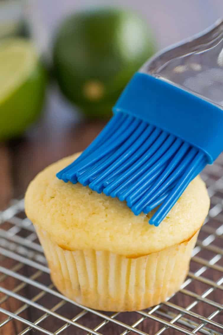 Margarita cupcakes prep: A vanilla cupcake is having tequila brushed on top with a pastry brush.