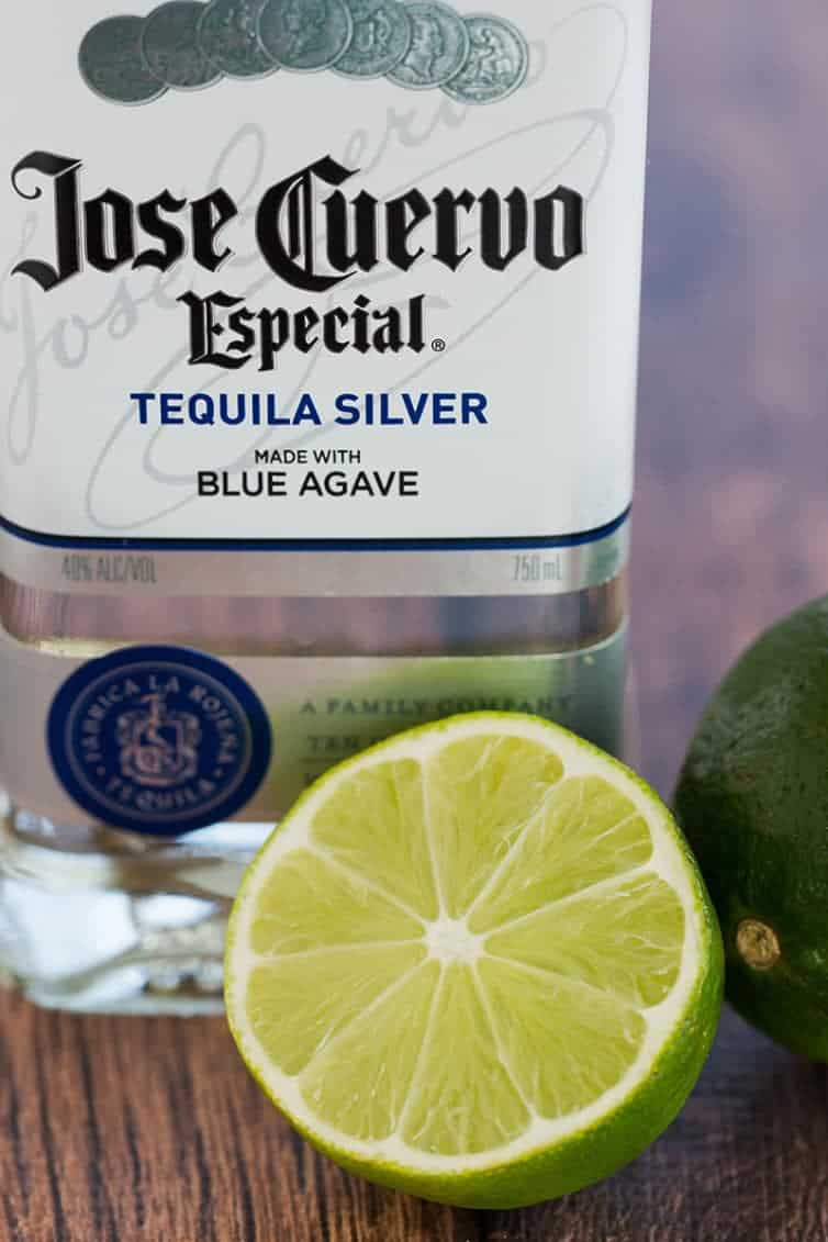 Prep for margarita cupcakes: a bottle of silver tequila and halved lime.