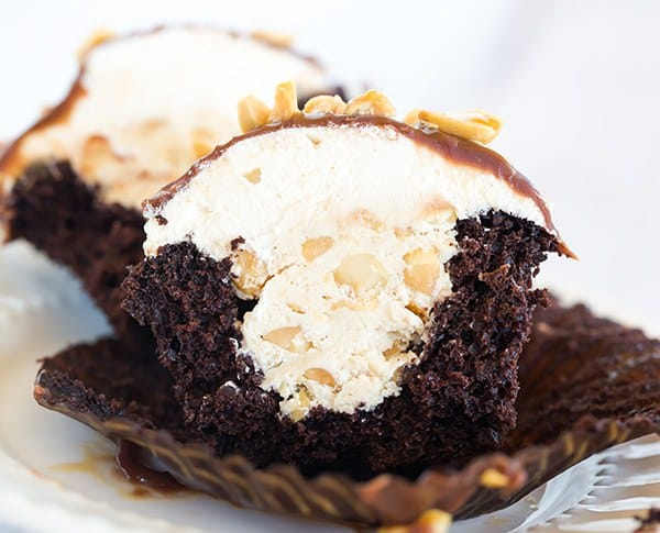 These Snickers cupcakes taste JUST like the candy bar... A chocolate cupcake filled with peanut nougat, topped with a caramel buttercream frosting, covered in a chocolate ganache, chopped peanuts and a drizzle of caramel sauce.