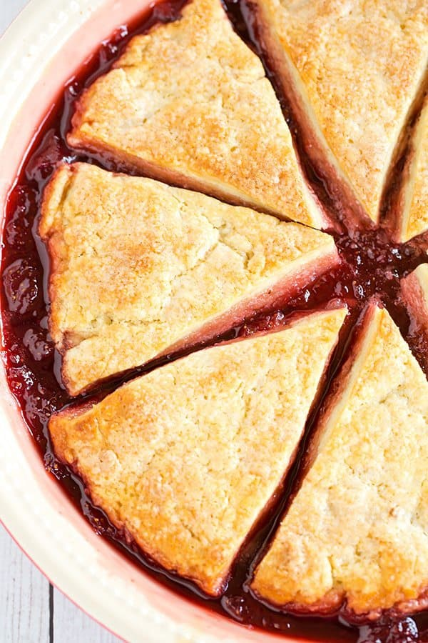Cobbler-style biscuits are nestled on top of fresh strawberry jam and baked until bubbling and golden. A wonderful summer dessert!