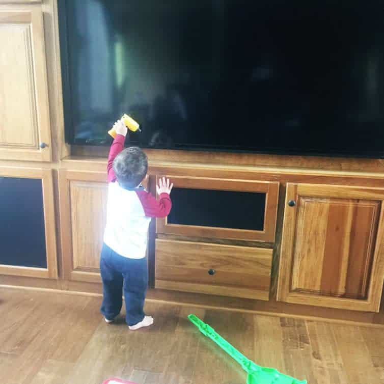 Joseph trying to fix the TV with his toy drill.