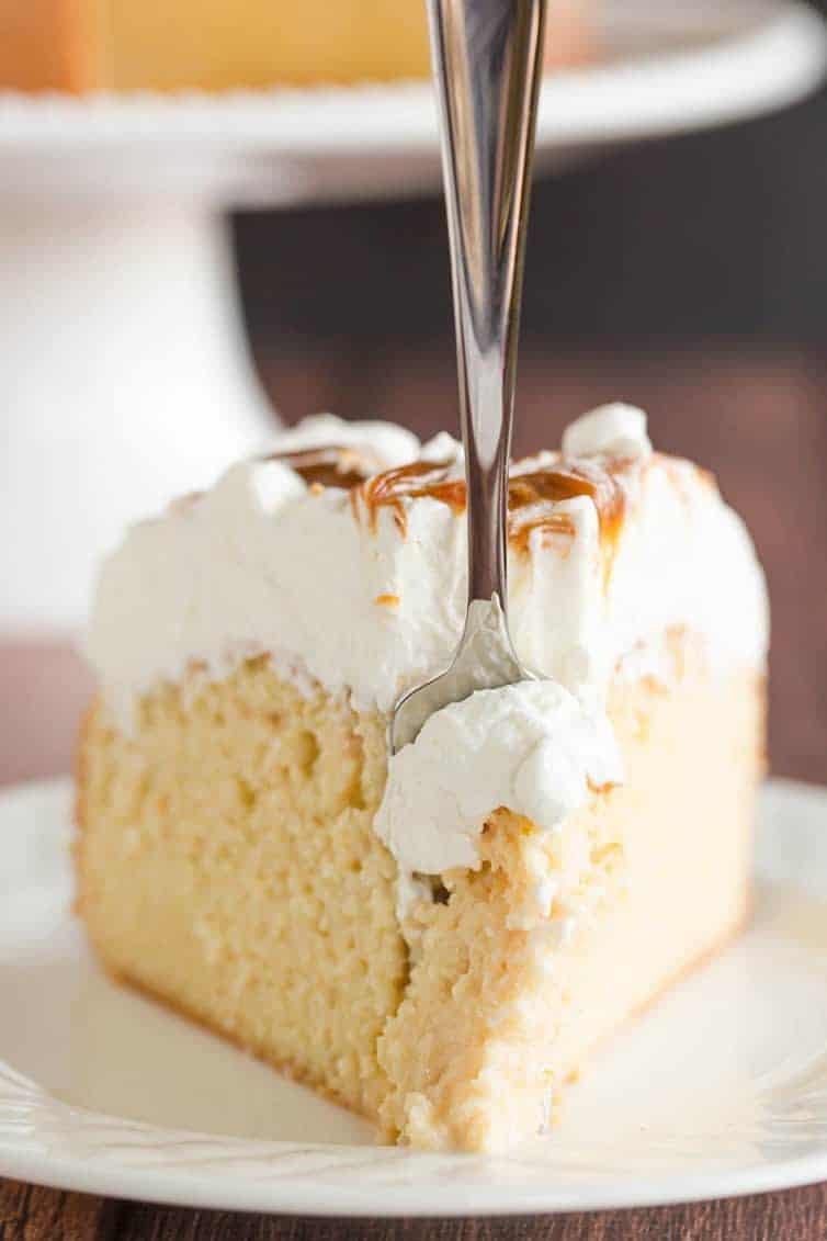 Take a big forkful of a slice of caramel tres leches cake.