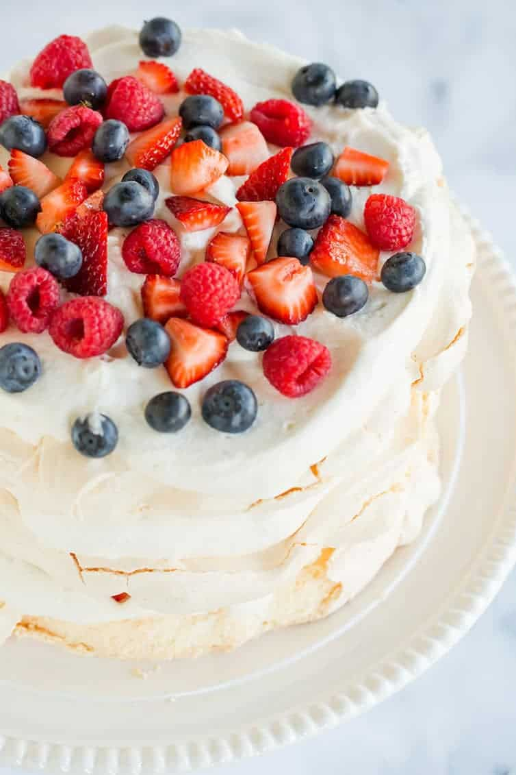An overhead view of a pavlova layer cake with whipped cream and berries.