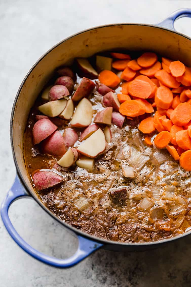 A pot of beef stew partially cooked with potatoes and carrots added in.