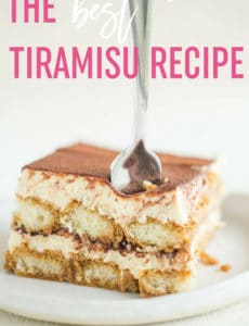 A slice of tiramisu on a white plate with a fork sticking out of the top and the words the best tiramisu recipe at the top.