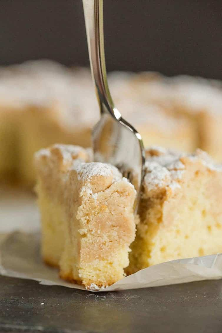 A fork cutting into a piece of crumb cake.