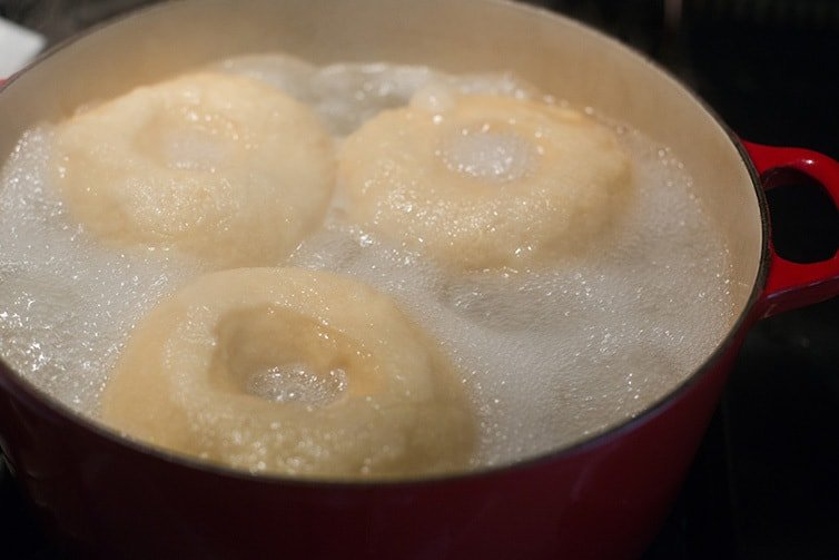 Bagels being boiled in water.
