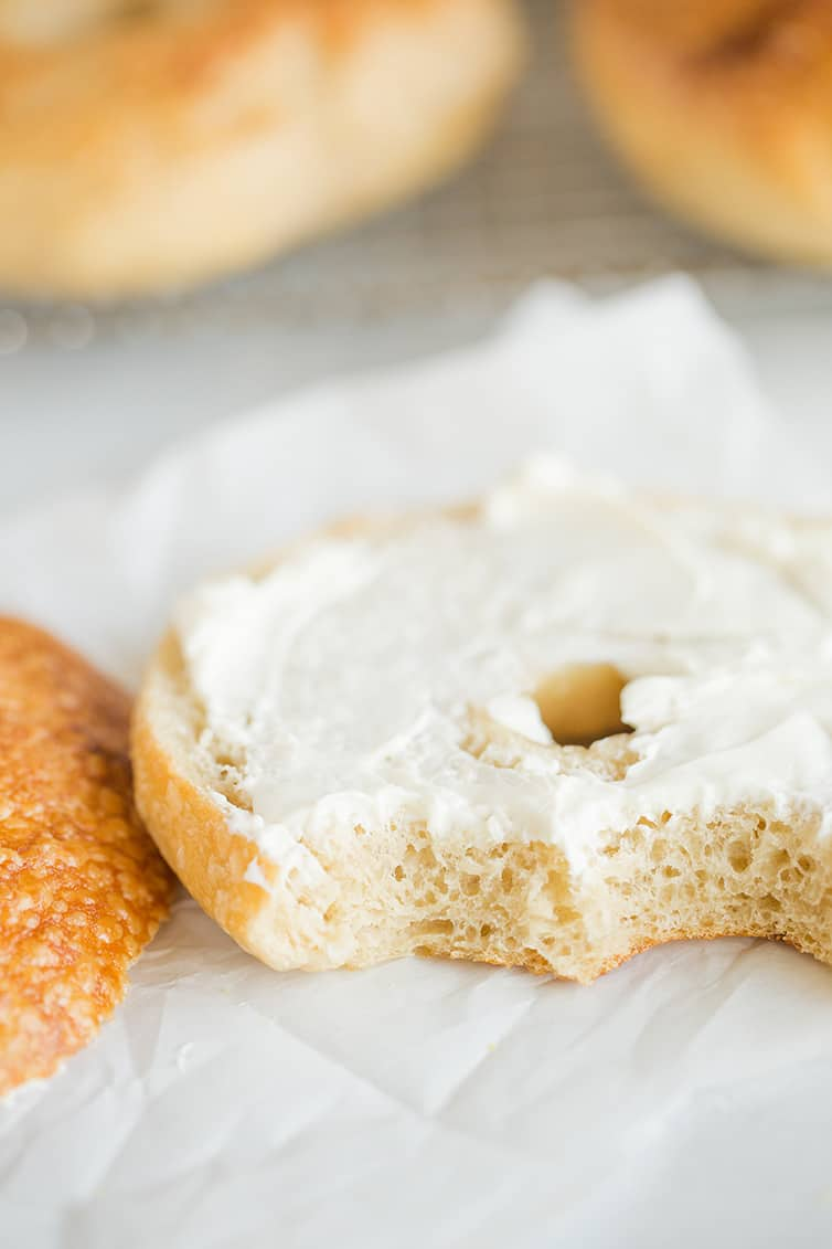Half of a bagel spread with cream cheese and two bites taken out.