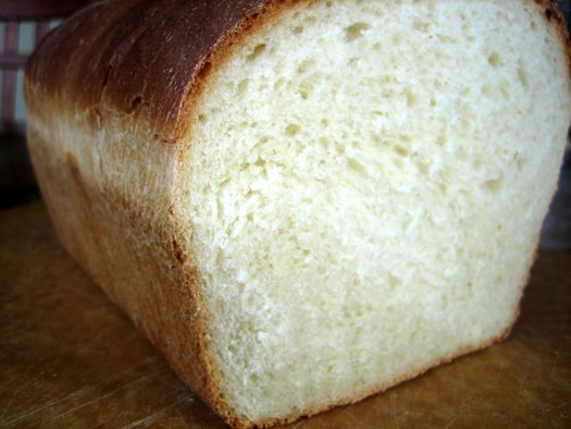 Sandwich bread loaf with a slice cut off showing the bread texture.