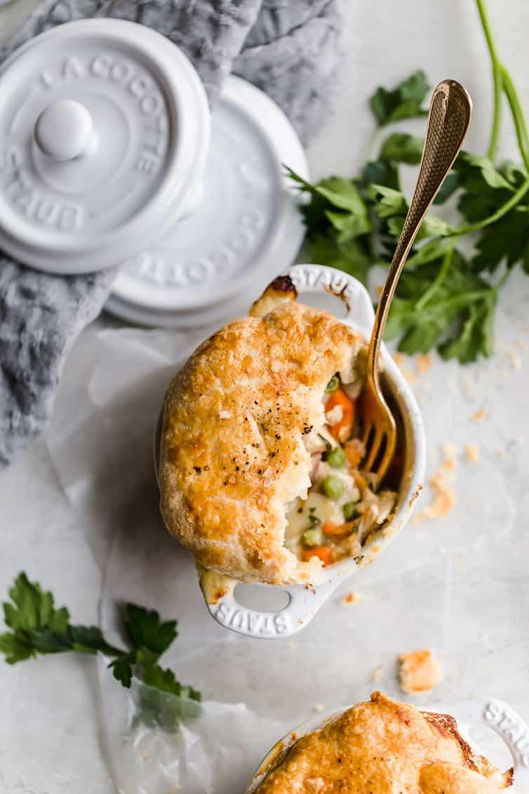 An overhead shot of a half-eaten ramekin of chicken pot pie.