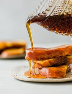 Close up of syrup being poured over three slices of French toast.