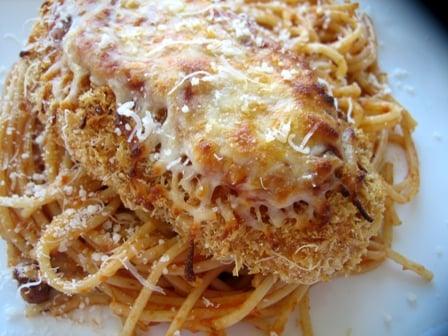 Chicken parmesan on top of noodles on a white plate.