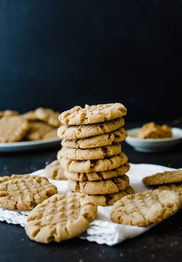 A stack of peanut butter cookies with additional cookies on a napkin.
