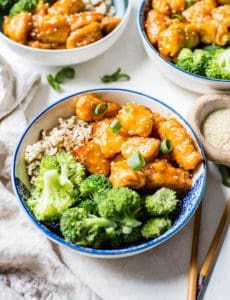 Three bowls of sweet and sour chicken with rice and broccoli.
