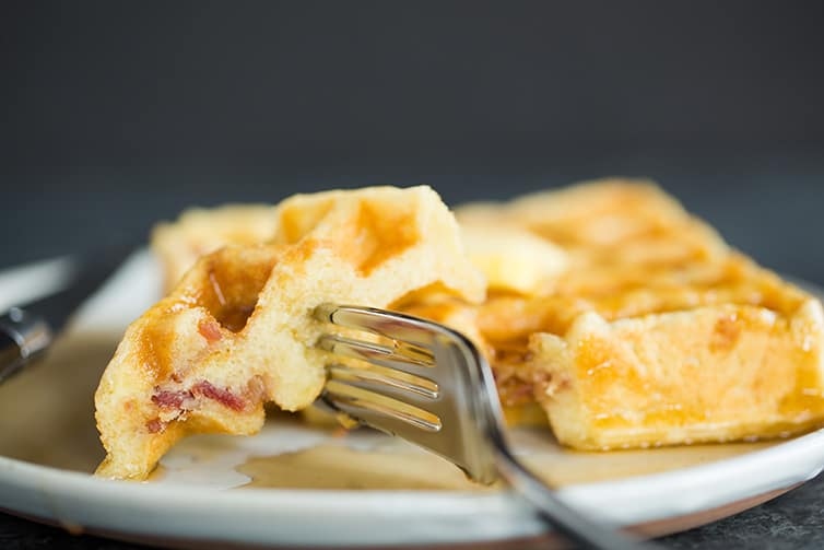 Taking a big bite of Brown Sugar-Bacon Buttermilk Waffles