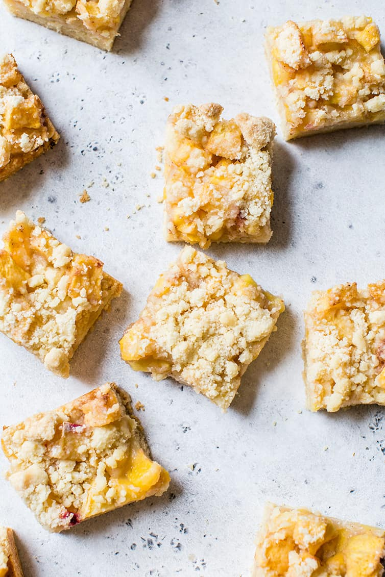 Squares of peach crumb bars on a serving platter.