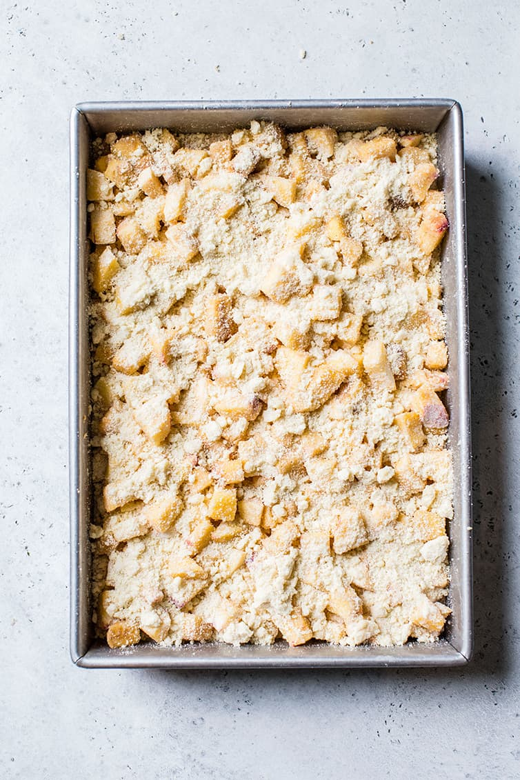 A pan of peach crumb bars prepared before going into the oven.