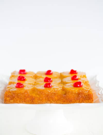A pineapple upside down cake set on a square white cake dish.