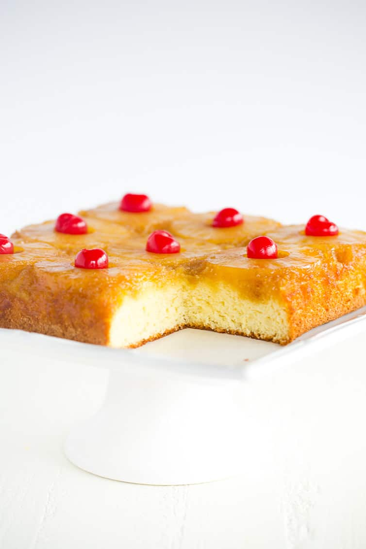 A pineapple upside down cake on white platter with a corner piece removed.