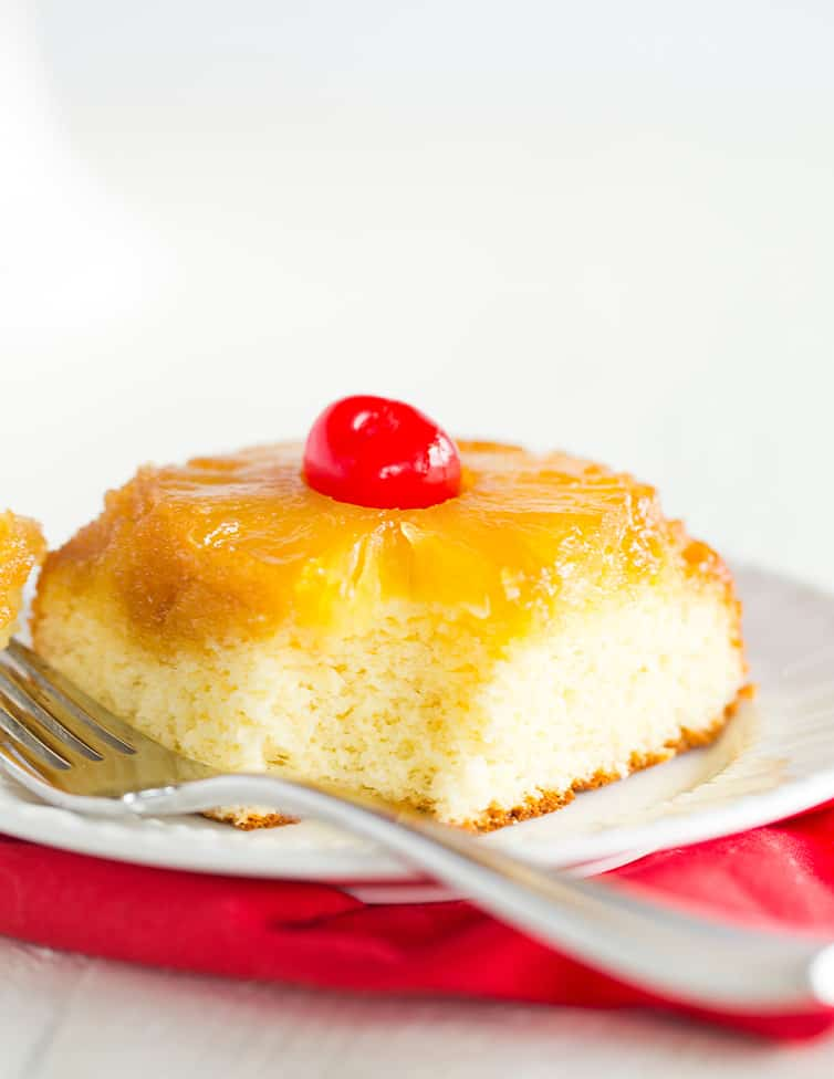 A piece of pineapple upside down cake with a bite taken out.