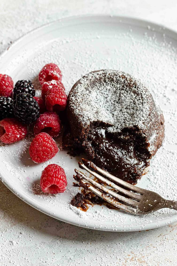 Chocolate lava cake on a white plate with a fork and raspberries.