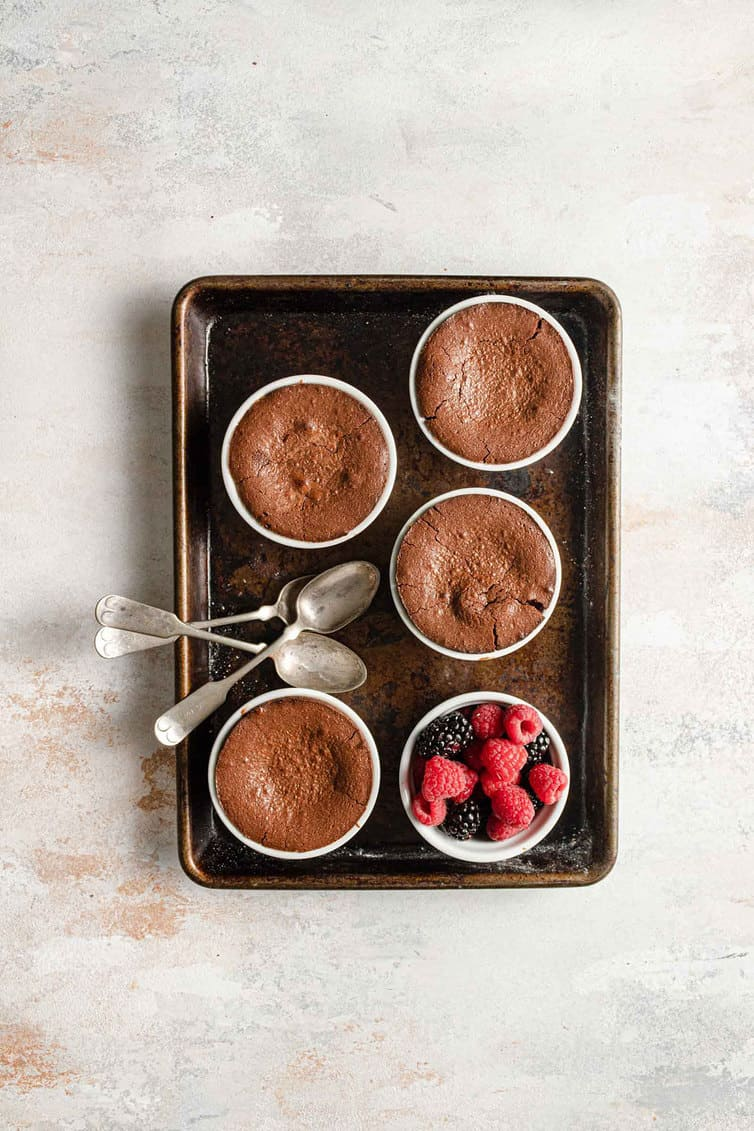 A baking sheet with four ramekins of baked chocolate lava cakes.