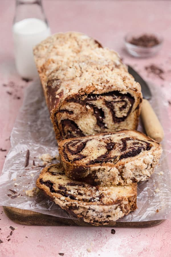 A loaf of chocolate babka with two slices laying in front.