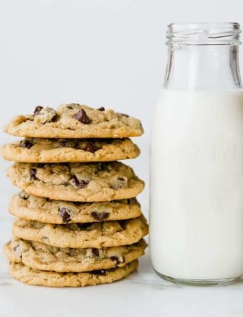 A stack of peanut butter-oatmeal chocolate chip cookies next to a glass bottle of milk.