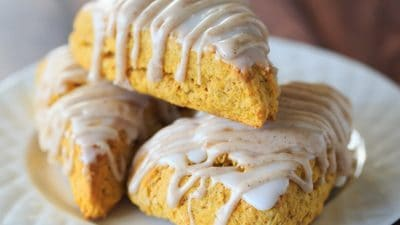 Pumpkin Scones with Spiced Glaze - A Starbucks copycat! | https://www.browneyedbaker.com/pumpkin-scones-spiced-glaze/