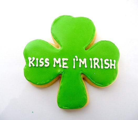 Shamrock sugar cookie with green icing and white lettering that says kiss me I'm Irish.