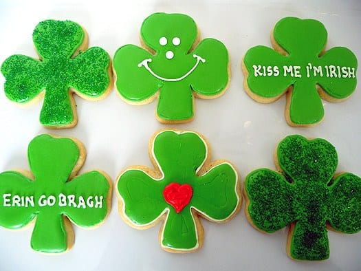 6 shamrock sugar cookies with green icing and piping decorations on a white plate.