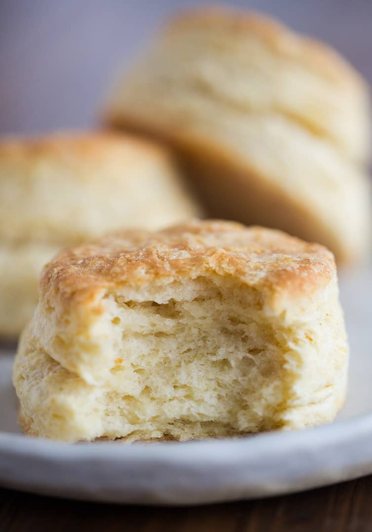 A tall, fluffy buttermilk biscuit with a big bite taken out.