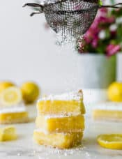 A stack of three lemon bars being sprinkled with powdered sugar.