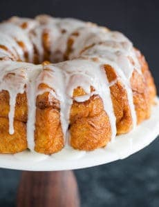 Baked and glazed monkey bread on a cake pedestal.