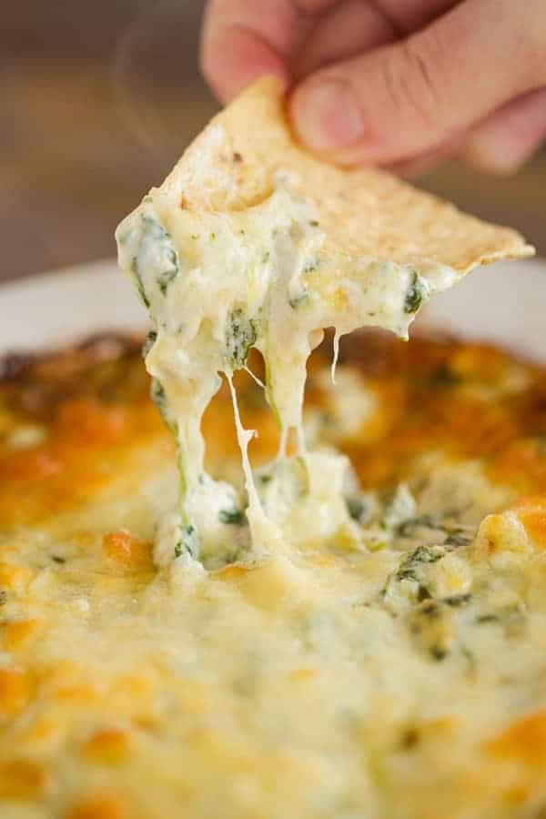 Dipping a tortilla chip into a pan of spinach artichoke dip.