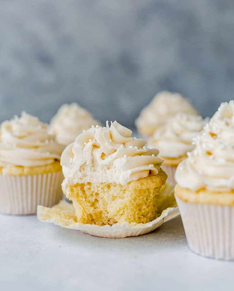 Vanilla cupcakes with a bite taken out of one.