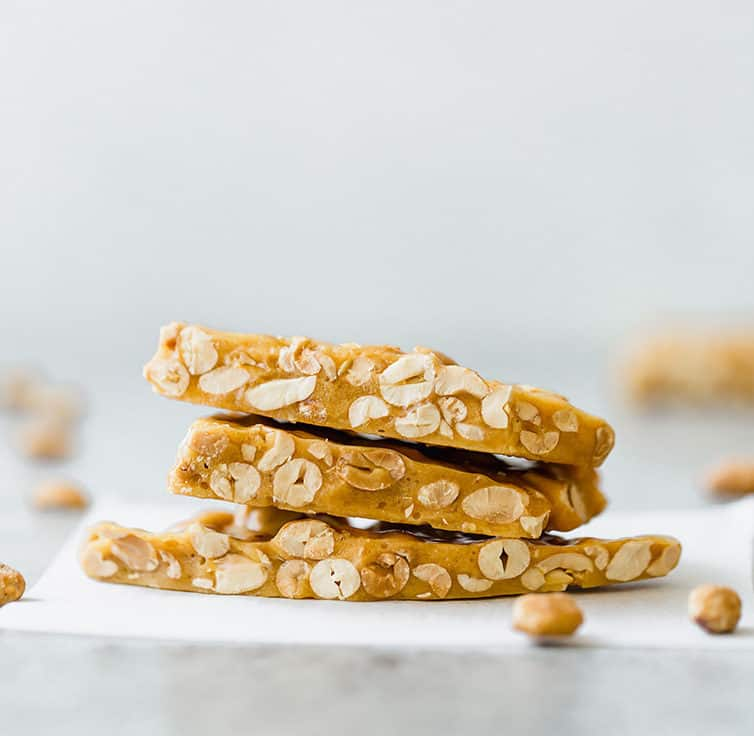 Three pieces of peanut brittle stacked on a piece of parchment paper.