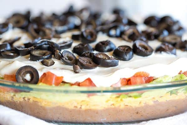 This Seven Layer Dip recipe is EASY and perfect for your Super Bowl party! Layers of refried beans, cheddar cheese, avocado, jalapeños, tomatoes, sour cream and olives! | browneyedbaker.com