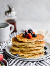 A stack of buttermilk pancakes with berries and a cup of coffee and syrup in the background.