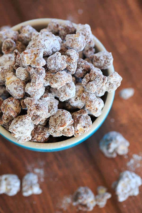 """This popcorn version of the enormously popular muddy buddies (or """"puppy chow"""") is chocolate and peanut butter-covered popcorn tossed in powdered sugar. 