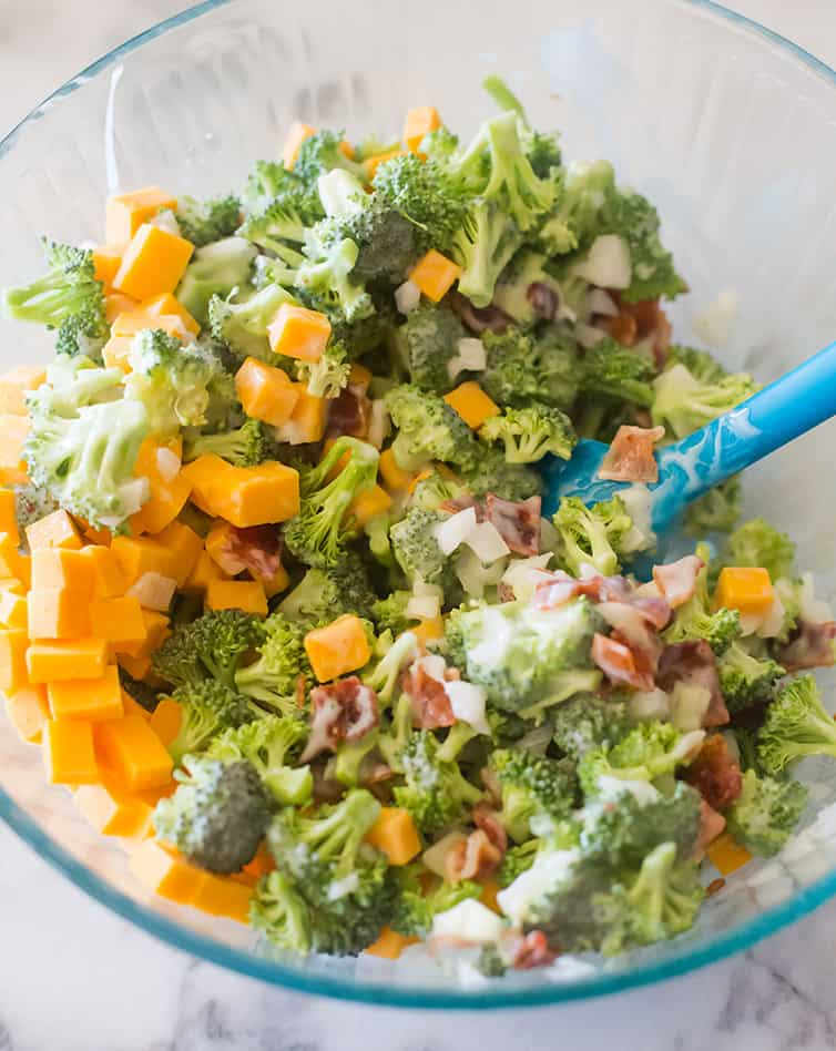 Stirring together a bowl of broccoli salad with dressing.