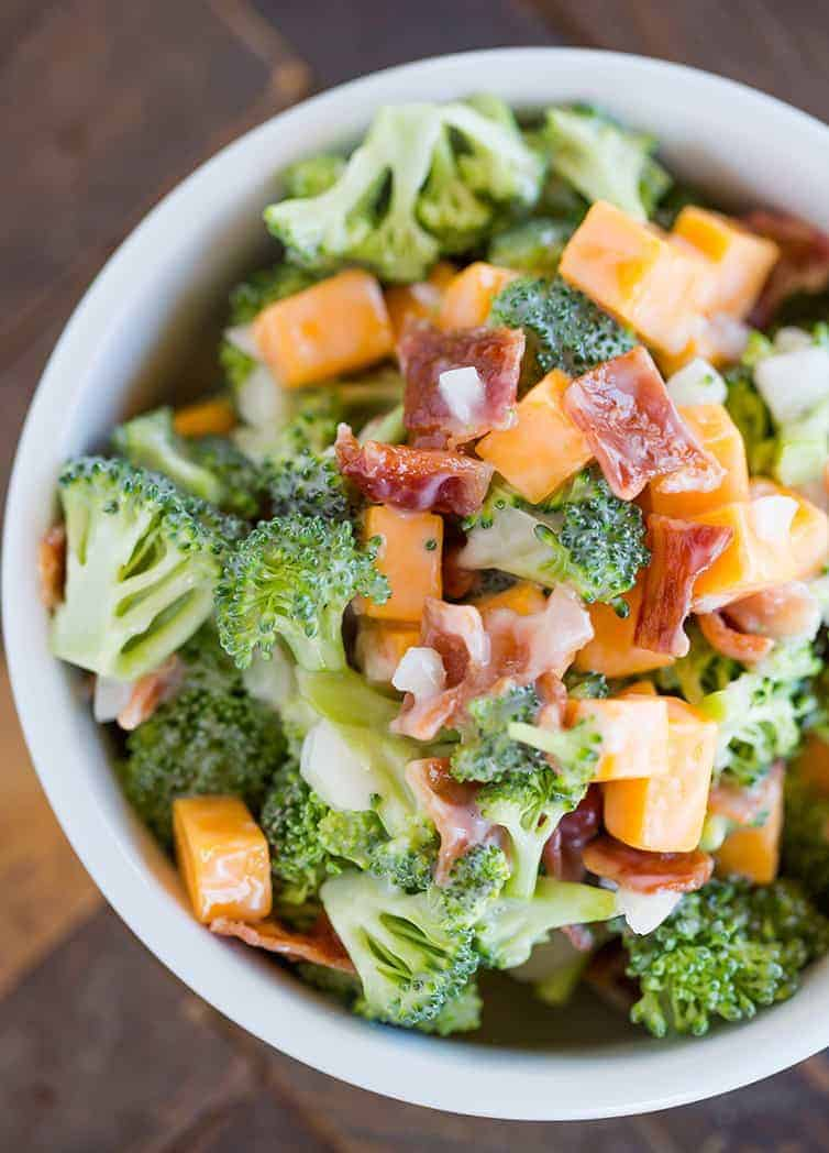 A bowl of broccoli salad with cheese and bacon.
