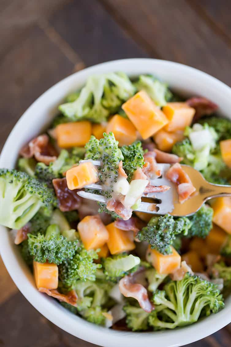 A forkful of broccoli salad with bacon and cheese.