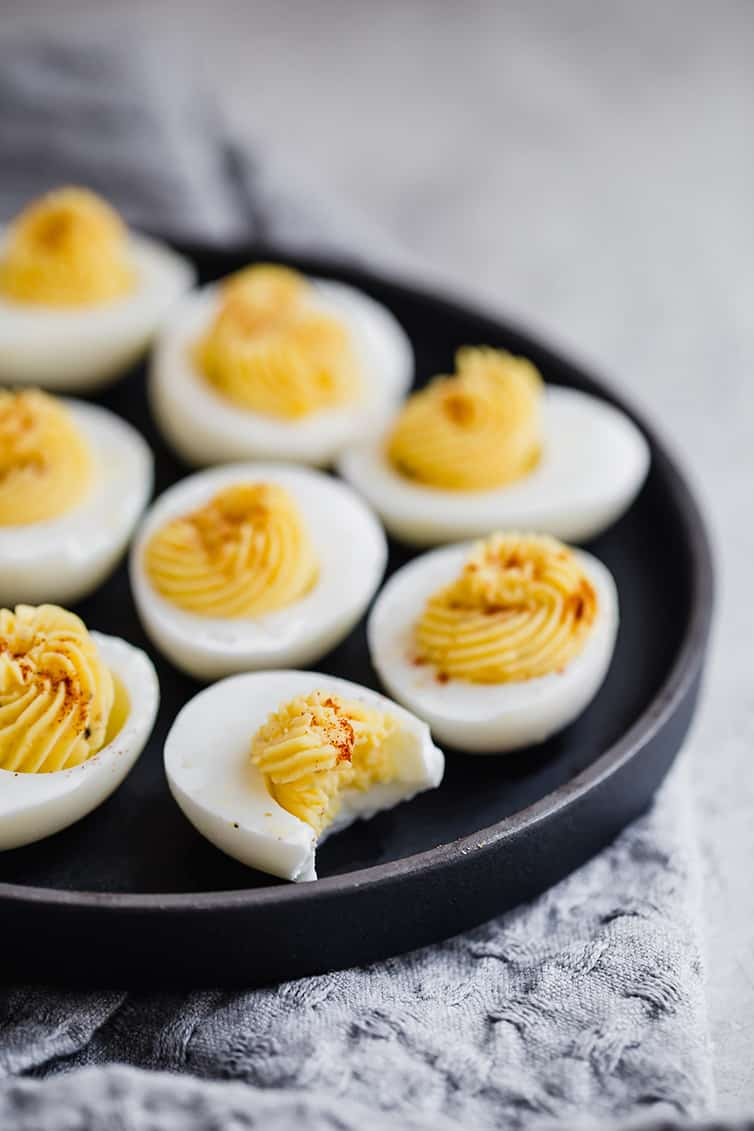 A black tray with filled deviled eggs.