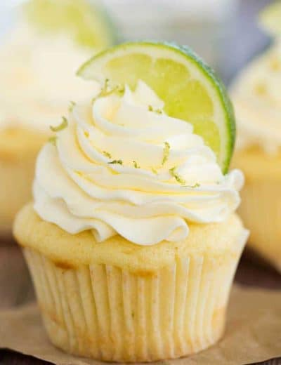 Vanilla cupcake topped with vanilla frosting, sprinkled with lime zest and topped with lime wedge.