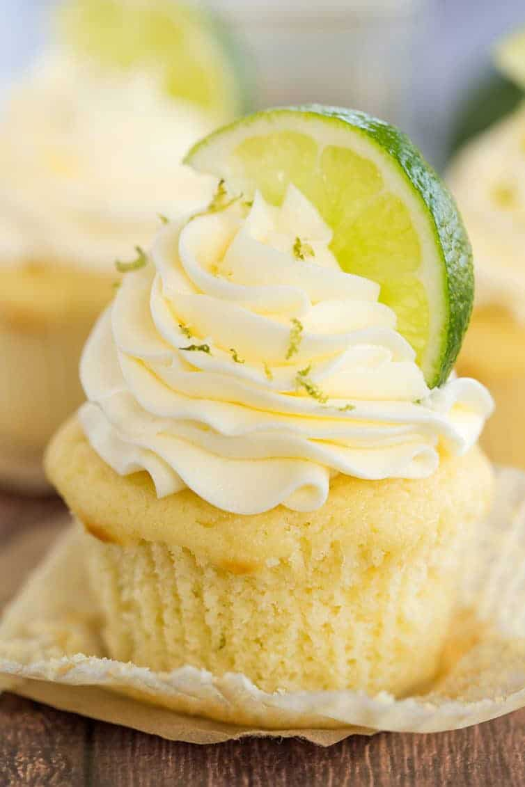 Margarita Cupcake - Vanilla cupcake with the paper liner pulled away. It's topped with lime zest and a lime wedge.