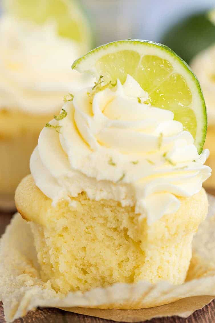 Margarita Cupcakes - A vanilla cupcake with vanilla frosting, lime zest and a lime wedge has a bite taken out of it.