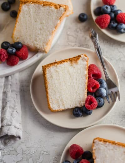 Three plates of angel food cake served with blueberries and raspberries.