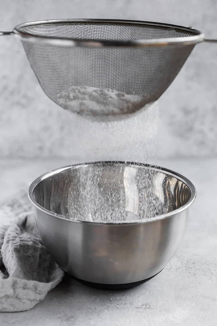 Sifting dry ingredients into a large stainless steel bowl.