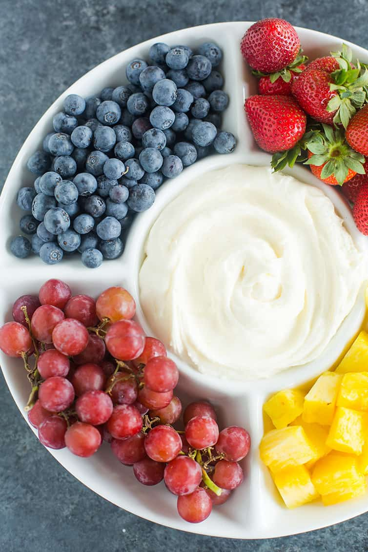A platter of blueberries, grapes, strawberries and pineapple with fruit dip.